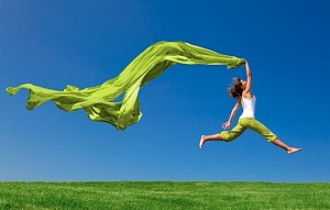 Beautiful young woman jumping on  a green meadow with a colored tissue